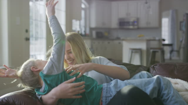playful girl carrying brother to sofa then tickling him / highland, utah, united states - fare il solletico video stock e b–roll
