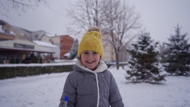 vídeos y material grabado en eventos de stock de chica juguetona sosteniendo un rascador de hielo mientras se divierte mientras nieva - admiración