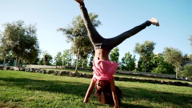vídeos de stock e filmes b-roll de playful girl in the park - braços no ar