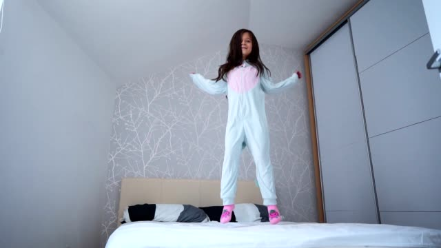 playful girl jumping on the bed - pyjamas stock videos & royalty-free footage