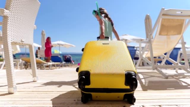 vidéos et rushes de fille espiègle tirant une valise jaune sur la plage tout en utilisant un masque de plongée - valise
