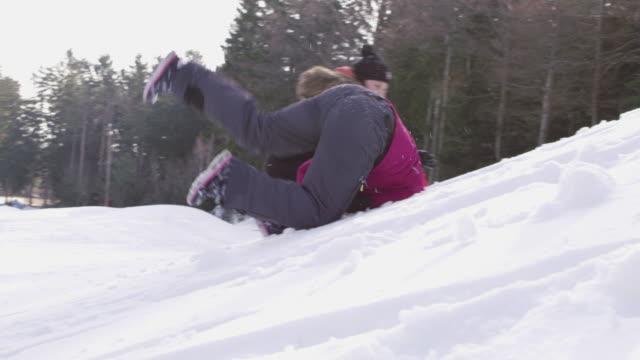 vídeos de stock e filmes b-roll de 4k playful girl rolling down snowy slope, slow motion - encosta