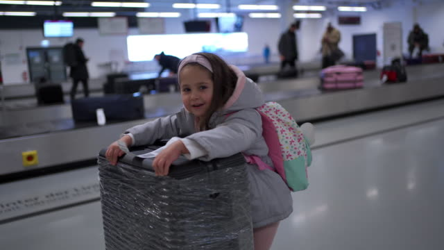 vídeos de stock e filmes b-roll de playful girl running at pushing suitcase at the airport - bagagem