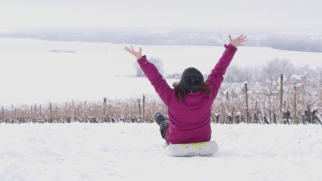 4K Playful girl sledding on snowy vineyard slope, slow motion