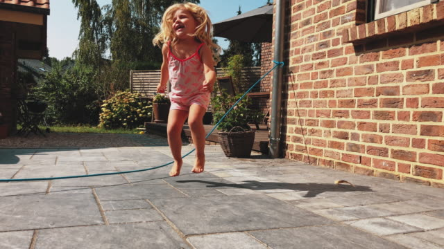 playful girl using skipping rope in backyard - skipping stock videos & royalty-free footage