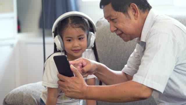 若い小さな男の子と女の子と一緒にスマートフォンのゲームをプレイする楽しみを持つ陽気な祖父は、自宅で無線技術を使用して、若い男の子と女の子との祖父を笑顔 - 子供2人の家庭点の映像素材/bロール
