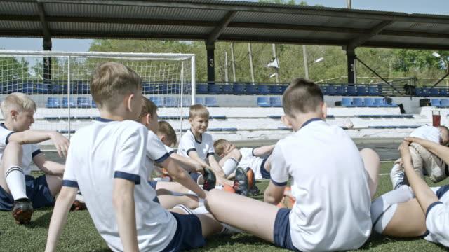 stockvideo's en b-roll-footage met playful kids doing butterfly stretch on soccer field - sunny