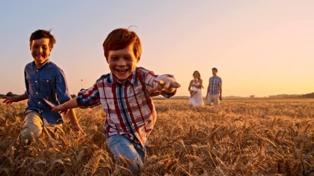 SLO MO lekfulla barn kör i fältet