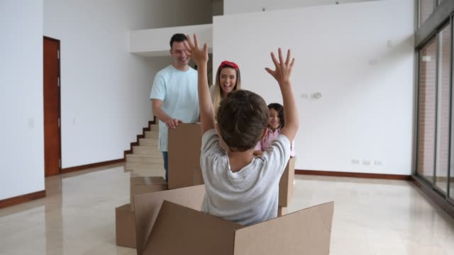 playful little boy surprising his family by jumping out of a cardboard box while his family is packing - trasloco video stock e b–roll