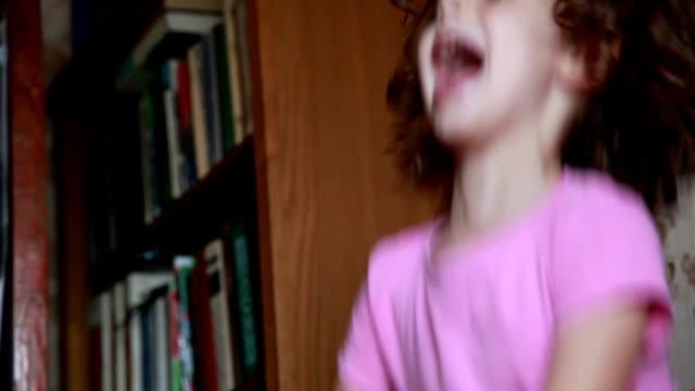 vídeos de stock, filmes e b-roll de menina brincalhão que salta e que grita - tendo o divertimento - cabelo encaracolado