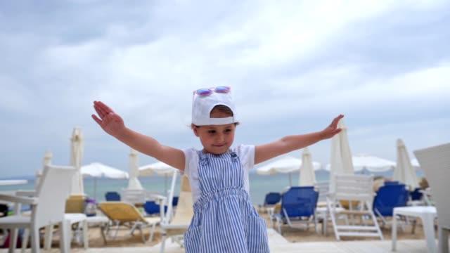 stockvideo's en b-roll-footage met speels klein meisje op het strand - haar naar achteren