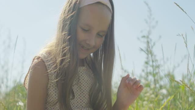 vidéos et rushes de playful little girl spinning a spinner sitting on green grass on field - seulement des enfants