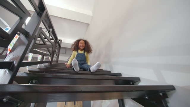vídeos de stock, filmes e b-roll de playful little girls sliding down the stairs - escadaria