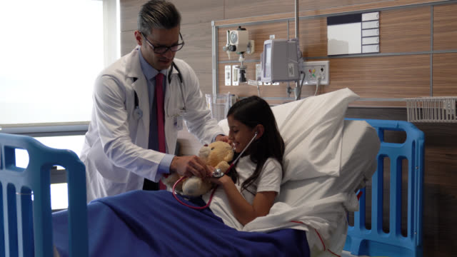 playful male paediatrician listening to heart beat of teddy bear with the help of hospitalized little girl - teddy bear stock videos and b-roll footage