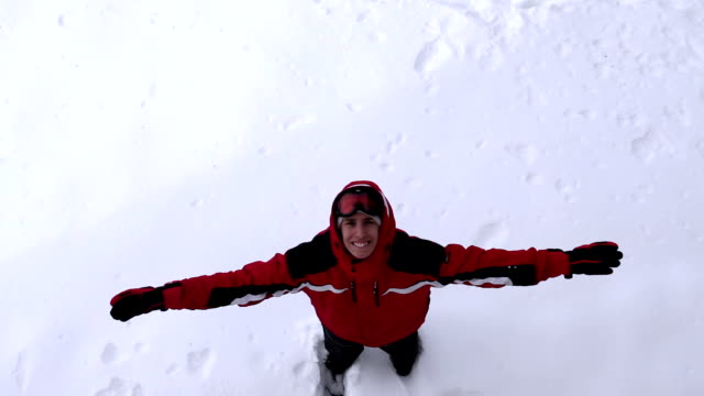 playful man makes snow angel - jacket stock videos & royalty-free footage