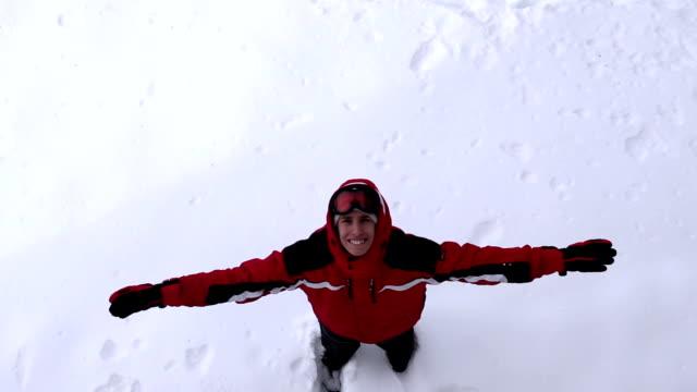 playful man makes snow angel - jacka eller kavaj bildbanksvideor och videomaterial från bakom kulisserna