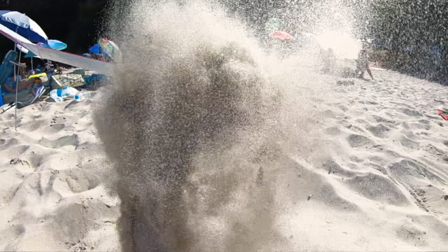 playful man throwing sand at beach - digital camcorder stock videos & royalty-free footage