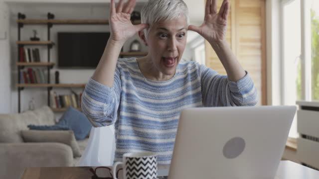 vidéos et rushes de femme d'âge mûr ludique faisant face et sortir la langue tout en utilisant l'ordinateur portable et d'avoir un chat vidéo avec quelqu'un. - tongue