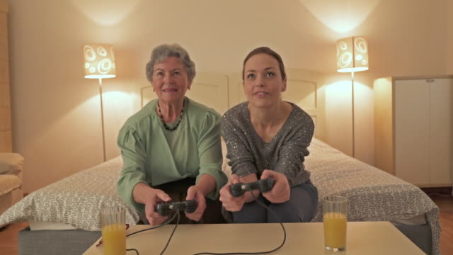 Playful mid adult woman and her other playing video game at home.