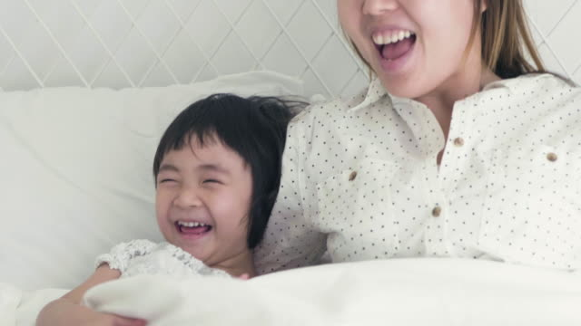 playful mother and daughters family sitting in bedroom - gratuity stock videos & royalty-free footage