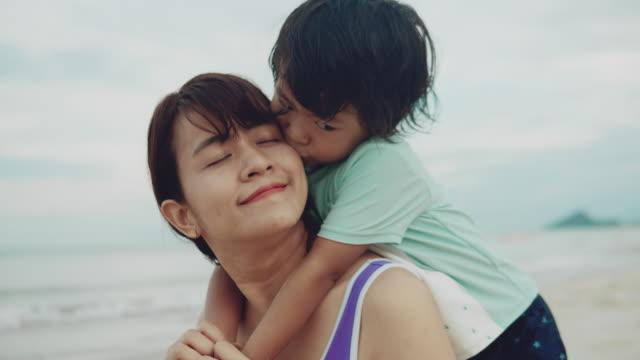 肩に娘を運ぶ遊び心のある母親、晴れた夏の海で回転 - おんぶ点の映像素材/bロール