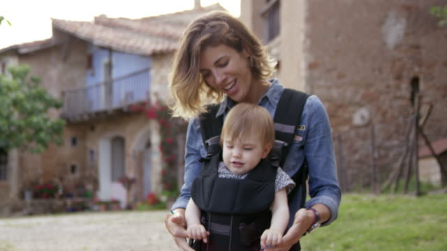 playful mother with daughter in backyard - baby carrier stock videos & royalty-free footage
