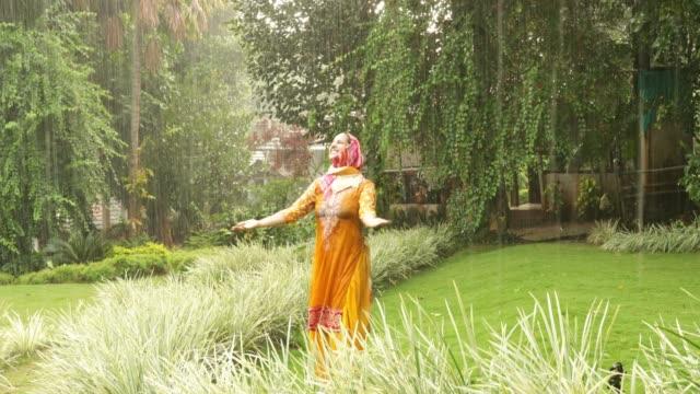 playful muslim woman enjoying rain - wet wet wet stock videos & royalty-free footage