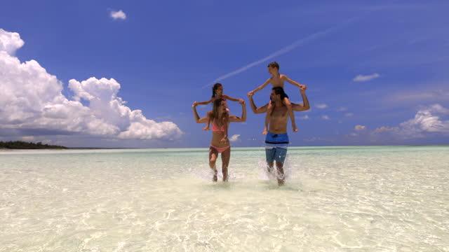 verspielte eltern laufen durchs meer, während sie ihre kinder auf schultern tragen. - beach holiday stock-videos und b-roll-filmmaterial