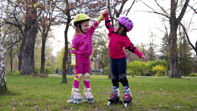 playful siblings on roller skates at a park - family with two children stock videos & royalty-free footage