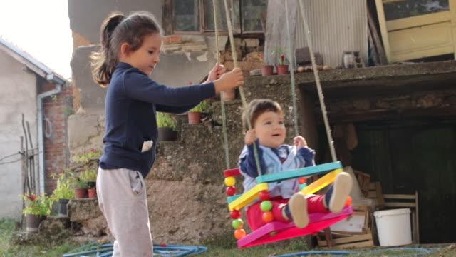 晴れた秋の日に村の家の裏庭でスイングで彼女の弟を振る遊び心のある姉妹 - 屋外遊具点の映像素材/bロール