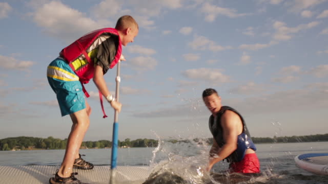 playful son splashing water on father with oar while standing on paddleboard at lake - giacca di salvataggio video stock e b–roll
