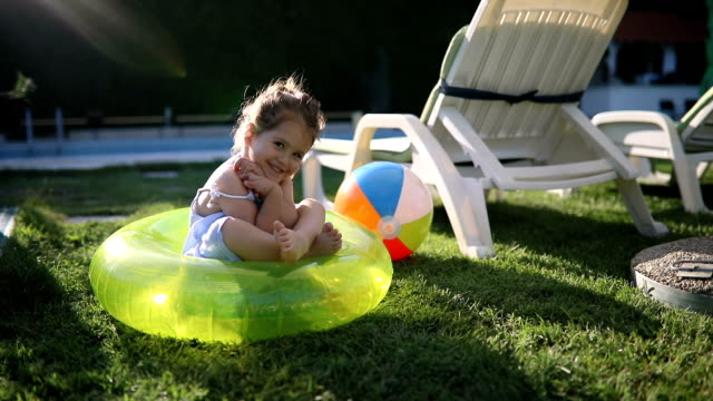playful toddler sitting in a inflated ring - outdoors stock videos & royalty-free footage