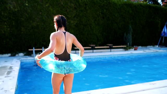 vídeos y material grabado en eventos de stock de mujer juguetona en la piscina - en el borde