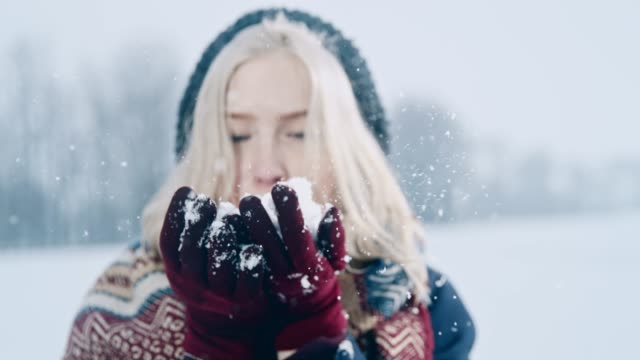 Playful woman blowing snow towards camera, super slow motion