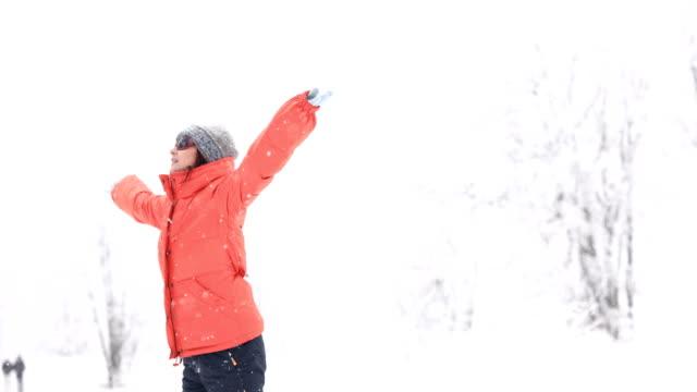 Playful woman enjoying the snowfall