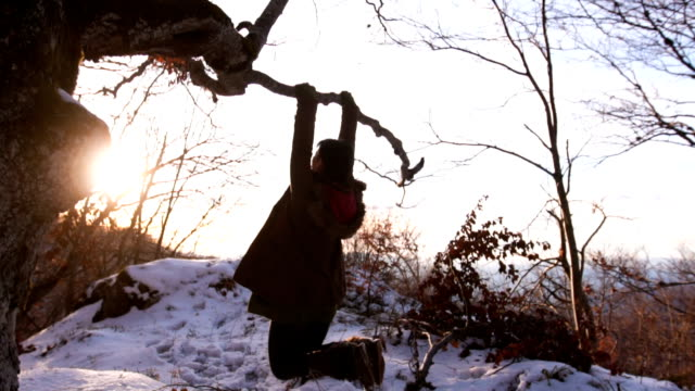 Playful woman hang from the branch