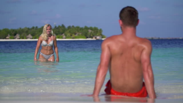 a playful woman splashes water on a man on the beach at a tropical island resort hotel. - slow motion - badeshorts stock-videos und b-roll-filmmaterial