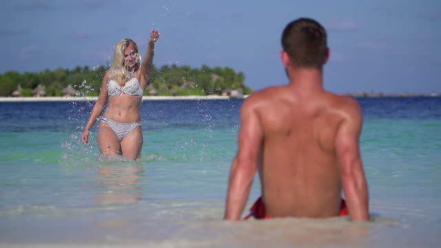 a playful woman splashes water on a man on the beach at a tropical island resort hotel. - slow motion - swimming shorts stock videos & royalty-free footage