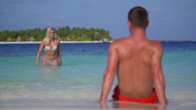 a playful woman splashes water on a man on the beach at a tropical island resort hotel. - swimming shorts stock videos & royalty-free footage