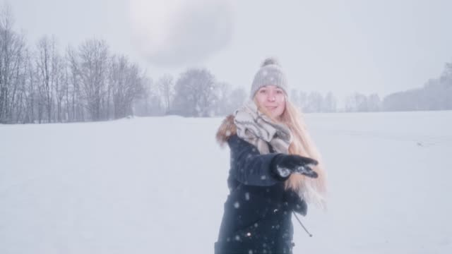 vídeos de stock e filmes b-roll de playful woman throwing snowball at camera, super slow motion - arremessar