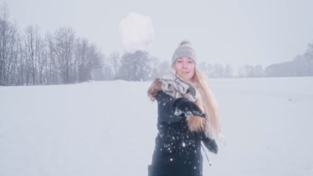 playful woman throwing snowball at camera, super slow motion - copricapo abbigliamento video stock e b–roll