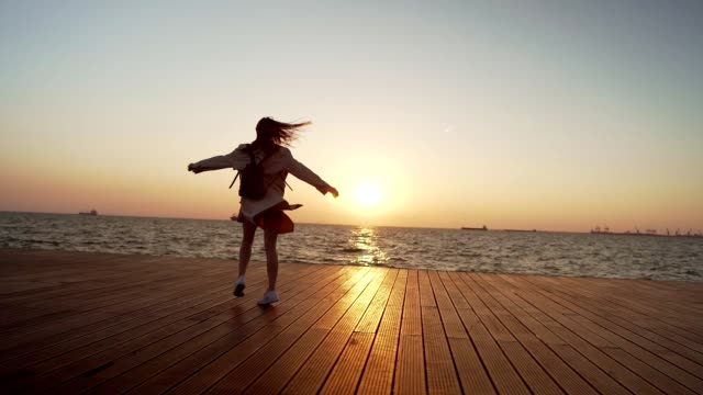 playful woman turning around at sunset - escapism stock videos & royalty-free footage