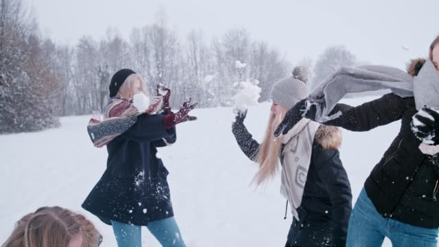 Playful women friends enjoying snowball fight, super slow motion