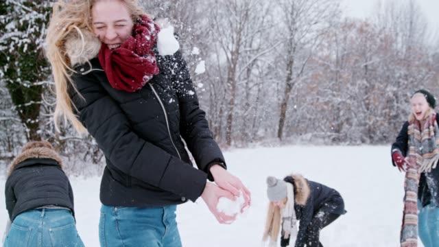 Playful women friends enjoying snowball fight, super slow motion