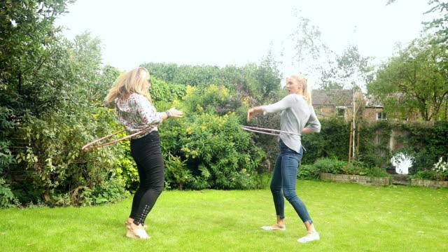 Playful women spinning in plastic hoops in backyard