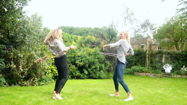 playful women spinning in plastic hoops in backyard - courtyard stock videos & royalty-free footage