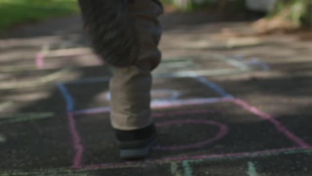 vidéos et rushes de playful young boy hops down a chalk drawn hopscotch on sidewalk - petits garçons