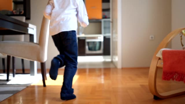 playful young boy running through the house - ambientazione interna video stock e b–roll
