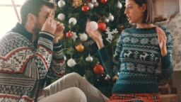 Playful young couple preparing gifts and decorating Christmas tree