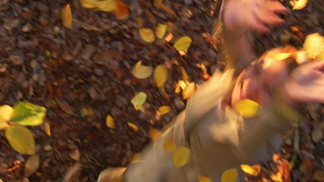 vidéos et rushes de ms joueuse jeune femme jetant l'automne doré laisse au-dessus de la tête dans la forêt - s'évader du réel
